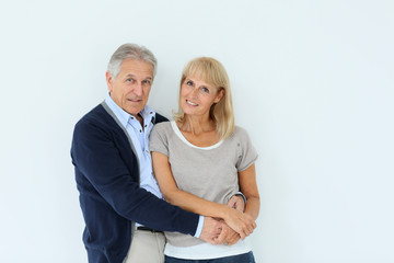 Portrait of senior couple embracing each other, isolated