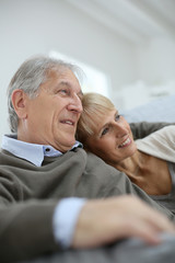 Senior couple relaxing in sofa and looking away