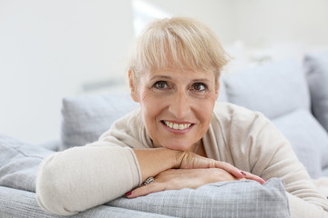 Portrait of smiling senior woman relaxing in sofa