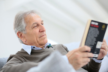 Senior man reading book relaxed in sofa