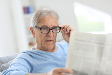 Senior man at home reading newspaper