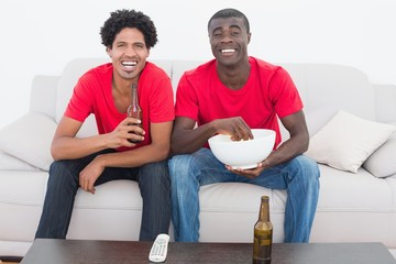 Football fans in red sitting on couch with beer and popcorn