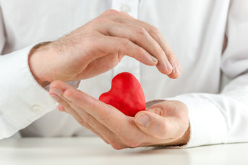 Caring man cupping a red heart in his hands