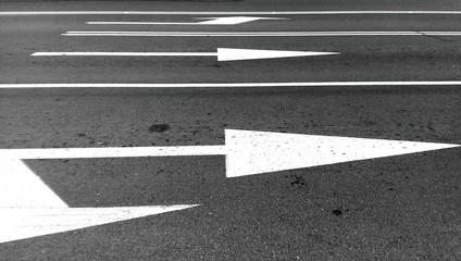 White arrows on asphalt road