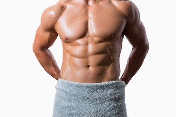 Mid section of a shirtless muscular man wrapped in white towel