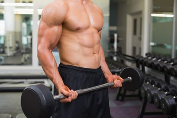 Mid section of shirtless muscular man lifting barbell