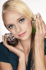 Blonde Frau mit zwei Parfum Flaschen