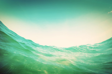 Water wave in the ocean. Underwater and blue sky. Vintage