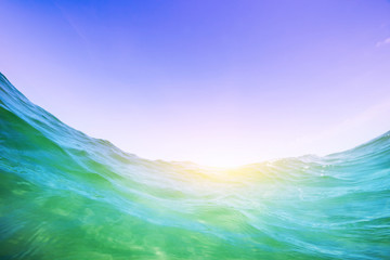 Water wave in the ocean. Underwater and blue sunny sky.