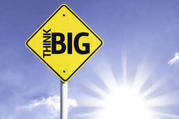 Think Big road sign with sun background