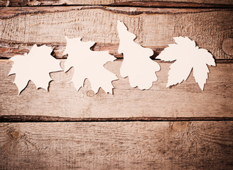 wooden background with paper leaves