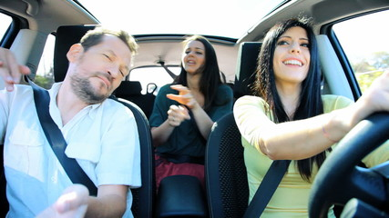 Two women and one man dancing in car driving