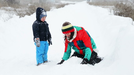 Mother and Son in Wintertime playing in snow