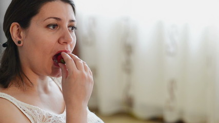 Pregnant woman eating strawberry