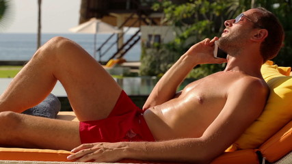 Young man talking on cellphone lying on sunbed by luxury villa