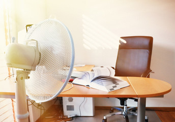 Fan in the office leafing a book