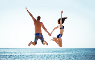 pretty young couple jumping near the sea