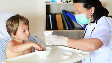 Kid eating and drinking under doctor observation