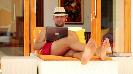 Young man with laptop lying on sunbed by luxury villa