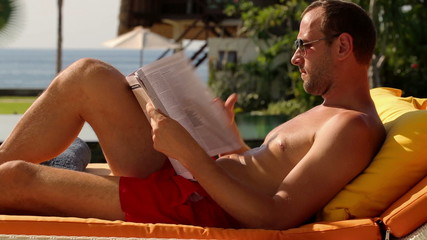 Young man reading magazine during sunbath on lounger
