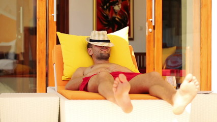 Young man sleeping while lying on sunbed by luxury villa