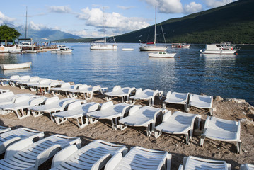 Deckchairs on the beach; boats tied up in the Bay of Herceg Novi