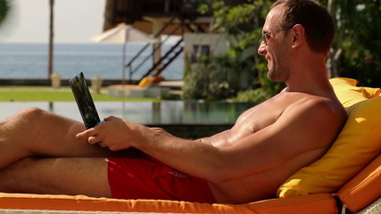 Man chatting on tablet while lying on sunbed at luxury garden