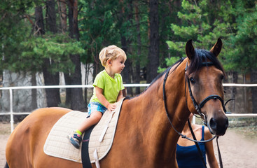 Two year boy drive astride horse