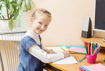 Cute smiling girl sitting at desk