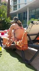 Mujer en bikini tomando el sol en una tumbona