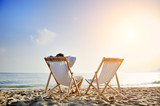 man relaxing on the beach sitting on deck chair