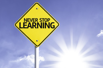 Never Stop Learning road sign with sun background
