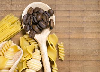 Kochlöffel mit Teigwaren und Kaffeebohnen auf einem Holzbrett