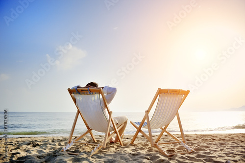 man relaxing on the beach sitting on deck chair - 67926506