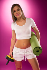 Fit woman carrying exercise equipment