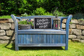 Blaue Bank in Garten vor Steinmauer