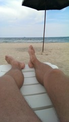 Male legs, sea coast, white lounge, relaxing on the sandy beach