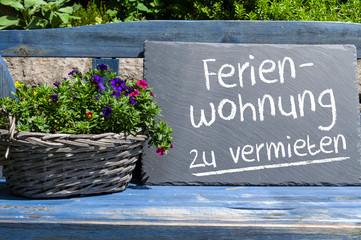 Blaue Holzbank mit Kreidetafel und Ferienwohnung