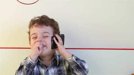 Laughing little boy talking on smartphone