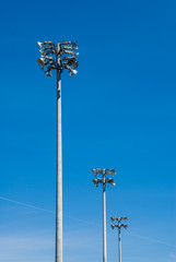 Row of stadium flood light towers on blue sky.