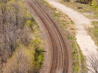 Pair of curving train tracks near forest.