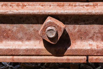 Rusted square bolt in metal rail.