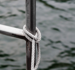 Rope tied to metal railing near water.