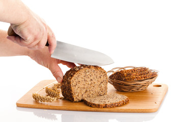 Fresh bread.  Slicing Bran Bread on a Cutting Board.  hands cutt
