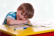 lächelnd legt ein Junge sein Kopf auf den Schreibtisch