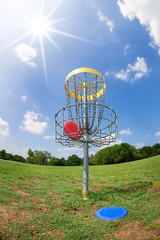 Disc golf basket in a park on a sunny summer day