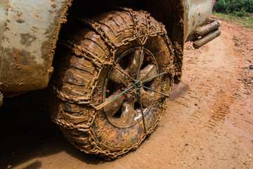 close up of off road car tire with chain on it