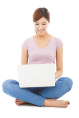 Smiling young woman sitting and using a laptop