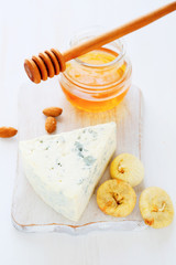 cheese, honey on a white chopping board