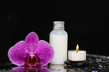 Pink orchid with candle and massage oil on wet background
